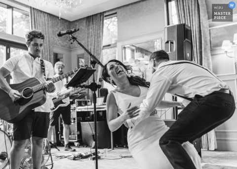 Wedding reception picture of bride dancing and falling by Hitchin, UK wedding photographer