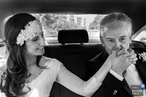 Bride in limo on wedding day | Kiss on hand from father