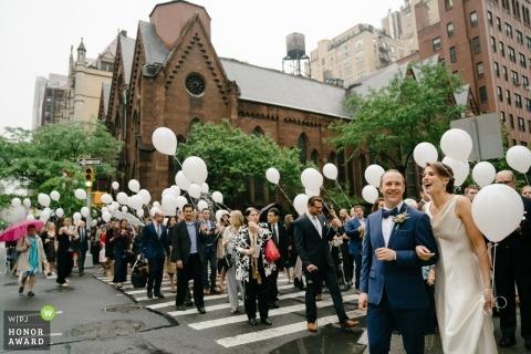 Casal de Nova York atravessando a rua com festa nupcial e convidados durante o casamento