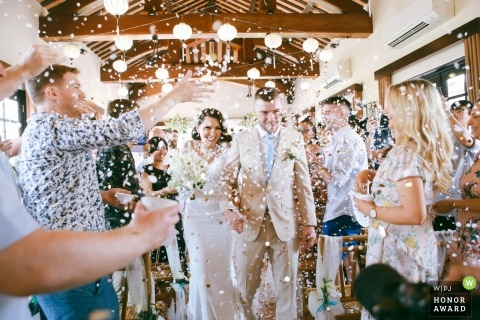 Wedding shoot with Quảng Nam couple walking through confetti shower following ceremony