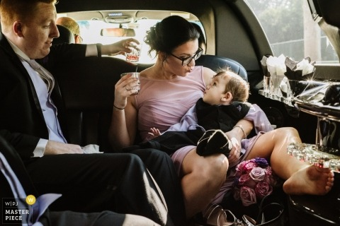 A bridesmaid makes a kissing face at a little toddler in her lap while they ride in a limousine. - Maid-of-Honor Duties