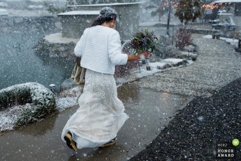 Genoa, NV documentary wedding photo of bride walking outside in falling snow