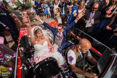 Hochzeitsfotografie der Braut und des Bräutigams, die weg in konvertierbares Auto reiten Hochzeitstagmomente in Northamptonship, Großbritannien