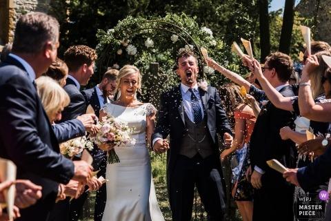 Hochzeitsfotografie aus Northamptonshire, UK von Braut und Bräutigam nach Zeremonie draußen gehen