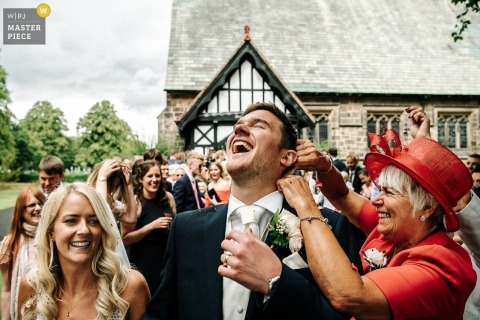Wedding photograph from Lancashire, England of mom pouring confettin down grooms shirt after ceremony