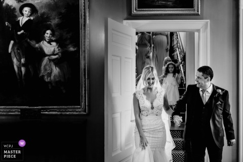 Wedding photograph of bride and groom walking into room - black and white | Wedding day moments captured in London