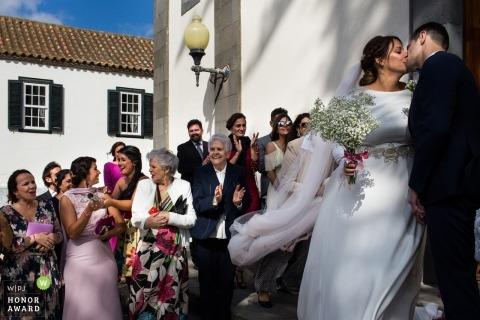 Fotos de una pareja besándose fuera de la iglesia por un gran fotógrafo de bodas en Gran Canaria, Islas Canarias