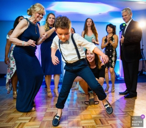 Photo d'une réception de mariage à Long Island, à New York, montrant un jeune garçon qui danse en regardant les invités
