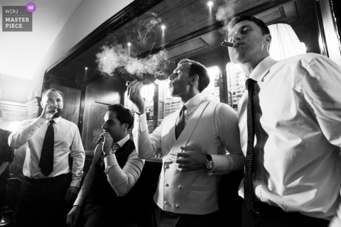 Wedding photo of the groom and best friends with cigars at the Villa Cora