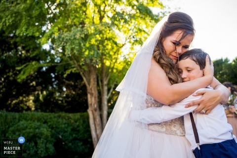 Wedding photograph of bride hugging young boy outside | Wedding day moments captured in Atlanta, Georgia
