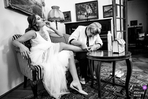 Wedding photograph of a Budapest bride getting help with her shoe during getting ready in Hungary