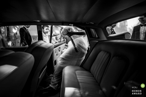 Wedding pictures of a bride entering limo with her bouquet by Budapest photographer