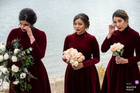 Alberta ceremony wedding photography of bridesmaids wiping tears by the lake