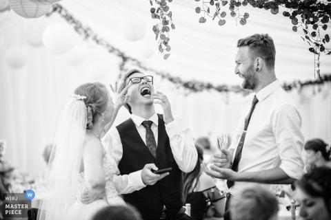Fotografia z wesela panny młodej Guernsey, która dzieli się śmiechem z gościem weselnym