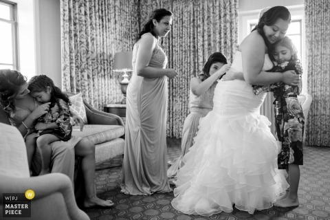 Wedding photograph of bride hugging young flower girl during getting ready in Washington DC