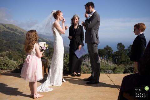 Big Sur, immagine di fotogiornalismo di nozze di CA di una coppia durante la cerimonia all'aperto | Una coppia bacia i loro anelli, recentemente benedetti, prima dei loro voti