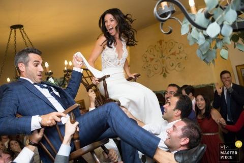 Een paar wordt gelanceerd in stoelen tijdens hun huwelijksfeest in Santa Barbara, Californië.