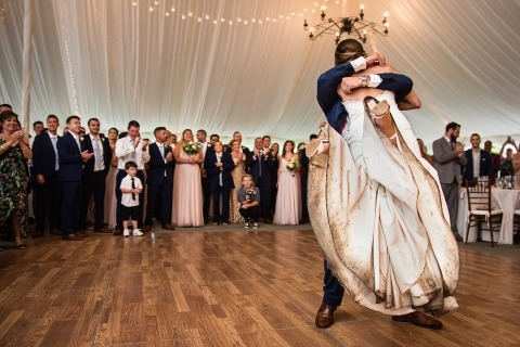 Bride with a really dirty wedding dress getting lifted up by the groom on the dance floor inside a tented reception | Rainy Wedding Photography
