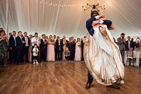 Mariée avec une robe de mariée vraiment sale soulevée par le marié sur la piste de danse à l'intérieur d'une réception sous la tente | Photographie de mariage pluvieux
