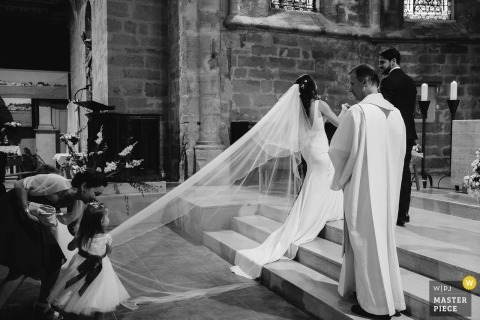 Florensac, France Church ceremony photograph of a young flower girl pulling on the brides Vail - Do not leave me alone