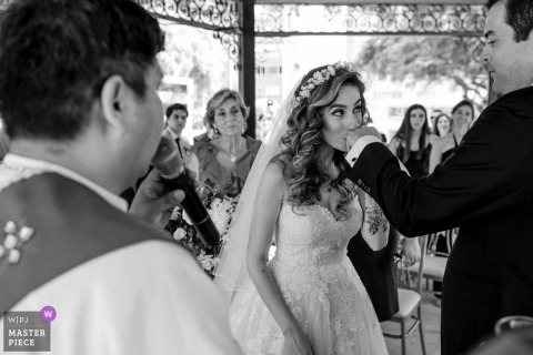 Wedding photograph from Club de Playa Solimar - the bright kisses the grooms hand during the ceremony - Lima, Peru wedding photographer