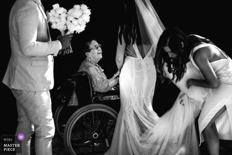 Fotografia ślubna Mont Du Soleil, Kalista, Australia trzymająca pannę młodą i rękę kobiety siedzącej na wózku inwalidzkim
