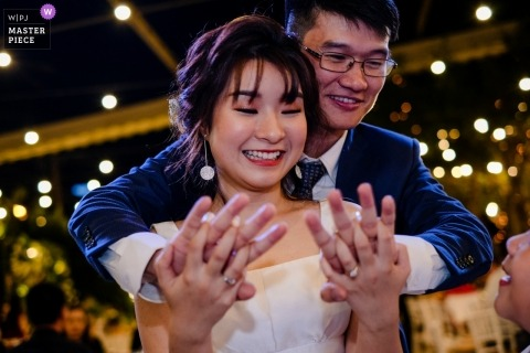 Ho Chi Minh City Wedding Day embrace for the bride and groom holding hands and looking at his ring on the dance floor