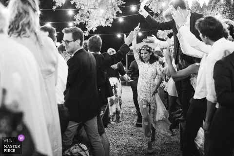 Villa Orlando, Torre del Lago, Lucca wedding photograph in black-and-white of the bride walking through the guests while celebrating