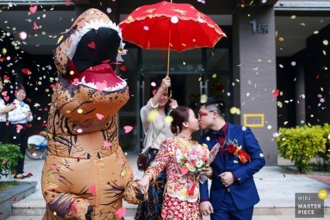Jour du mariage de la Chine à Zhuhai - La mariée et le marié embrassés avec des dinosaures