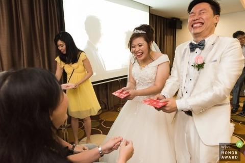 Orchid Country Club Singapore trouwfoto's | Het paar werd uitgelachen nadat ze het traditionele rode pakje van hun familie hadden ontvangen