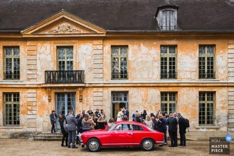 De ceremoniefoto van Parijs van een rode auto, de bruid en de bruidegom, en gasten