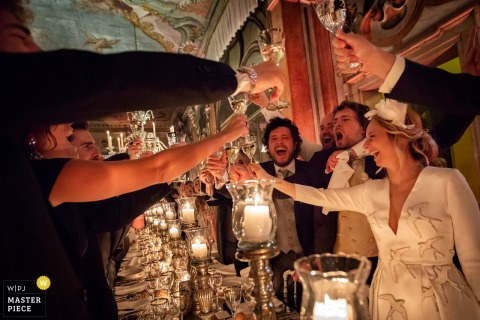 Venice - Pisani Moretta Palace wedding reception photograph of cheerful toast with friends