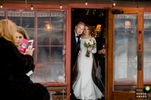 The father of the bride peeks out the door to get a look at the audience in attendance for his daughter's wedding ceremony at Elkins Resort on Priest Lake in Nordman, Idaho.