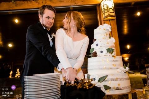 Les jeunes mariés réagissent presque à l'idée de renverser leur gâteau de mariage en le coupant lors de leur réception au Elkins Resort sur Priest Lake, à Nordman, dans l'Idaho.