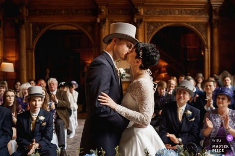 Devon, UK indoor wedding ceremony with tophats - Photo of the Bride and groom first kiss
