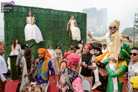 Mumbai, India weddings - photograph of Groom arrival with musicians in chairs hanging on an ivy wall