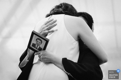 Otaki Rose Garden weddings - Love from the back. Photo of the bride hugging a Woman holding a photograph of a man