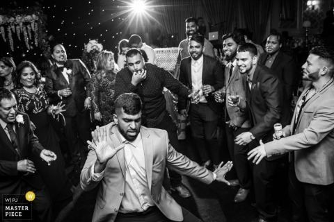 The groom on the dance floor surrounded by his friends at his wedding in Toronto, Canada.