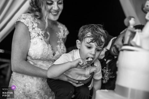 tort weselny siracusa - panna młoda trzyma małego chłopca, gdy smakuje ciasto