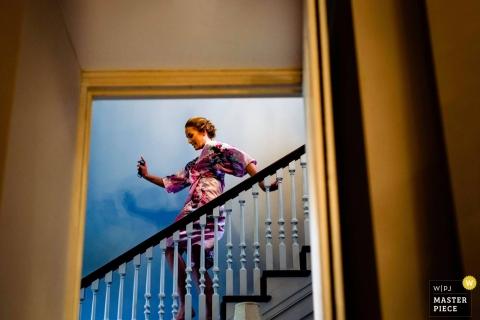Stanbrook abdij trouwfoto van een gelukkig bruidsmeisje dansen de trap af