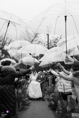 Zhuzhou, China wedding photo depicting Friends shielding the bride and groom from the rain during the ceremony
