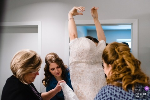 Omaha, NE photograph - Getting a bride dressed with her gown going over her head