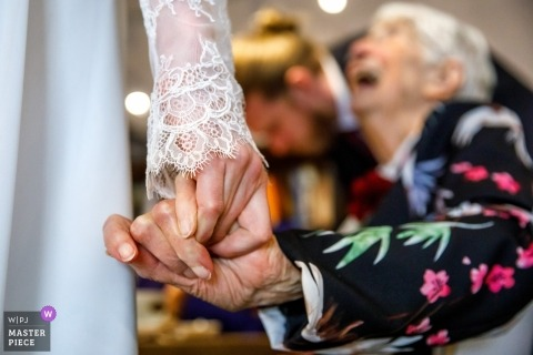 Osnabruck, NL what a photographer - grandma love is visible in this photograph of her holding hands with the bride
