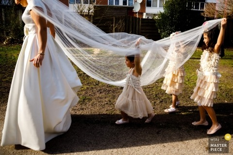 Netherlands wedding photographer - Hengelo bride with her veil being lifted by three young flower girls outside in the sun