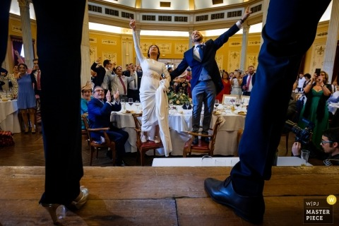 Photograph of the bride and groom celebrating during their wedding reception wall standing on their chairs