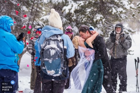 Mammoth Lakes, California wedding photograph - The bride and groom kiss during their wedding ceremony in blizzard, surrounded their friends and family.