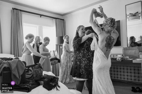 Santa Barbara, California wedding photo - The bride gets help from her family and friends as she puts her wedding dress on.
