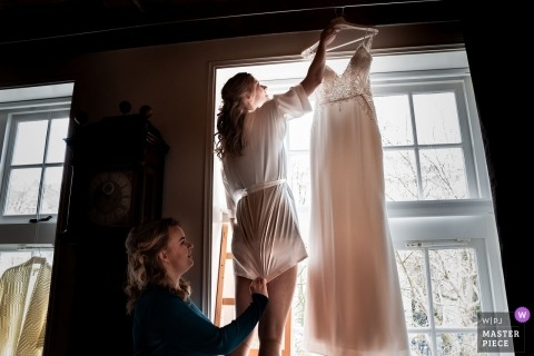 Spoorwegmuseum Utrecht, NL - The bride is preparing her dress so it can be photographed while hanging in the room. Her friend takes care of her short night dress that it won't crawl up and she pulls it down.