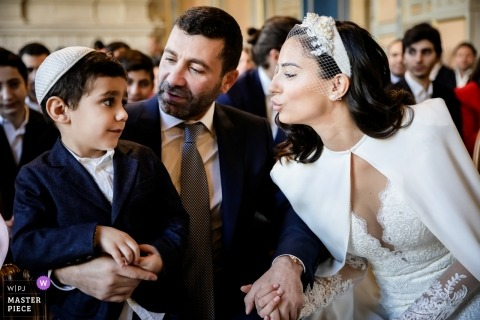 Paris - France Wedding Photography - I don't want a Kiss - a young boy is hesitant about receiving a kiss from The bride during the ceremony