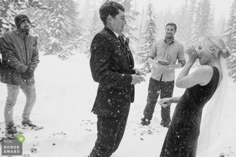 Mammoth Lakes, California elopement ceremony | Bride and groom adjust to the weather at the beginning of their wedding ceremony in blizzard conditions